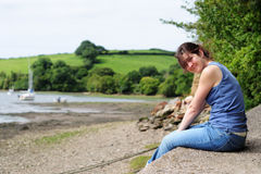 Resting at the creek. Female sitting on boat slip on a shingled beach and creek landscape Royalty Free Stock Photography