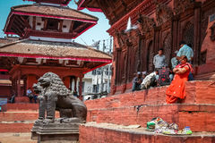 Resting in Durbar Sqare. People resting on steps of a heritage building with stone lions in the foreground, Durbar square in Kathmandu, Nepal Stock Photos