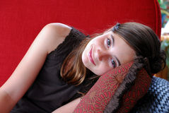 Resting Girl. Beautiful brown haired girl resting on a pillow on outdoor furniture Royalty Free Stock Image