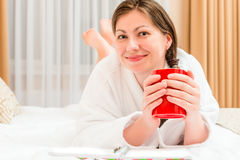 Resting girl in bathrobe drinking tea Stock Photography