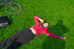 Resting on the grass. Young woman resting on the grass in the park after a bike ride. Bike next to her Royalty Free Stock Photography