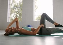 Resting at gym after exercising. Woman lying on exercise mat and smiling at the fitness club after training session Stock Images