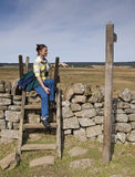 Resting on Hadrians Wall. A woman resting on a crossing stile at Hadrian's Wall royalty free stock images
