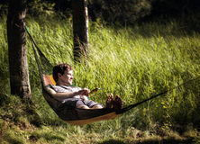 Resting in Hammock on Gorgeous Summer Evening. Jesse is relaxing in a hammock, enjoying a light breeze, on a beautiful summer day Royalty Free Stock Images