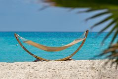 A Resting Hammock by Sea Beach, Empty Under Sunlight. Blue Sea in Background royalty free stock photo