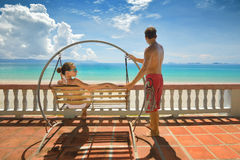Resting happy couple swinging on a swing looking at the blue sea Stock Image