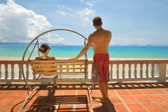 Resting happy couple swinging on a swing looking at the blue sea Stock Photos