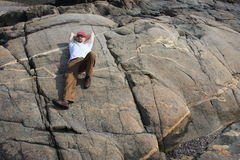 Resting After a Hike. Man resting in the sun on a large flat rock on the oceanside after a hike Stock Photography