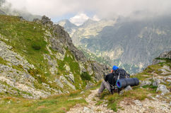 Resting hiker admiring views on a mountain trail. Royalty Free Stock Images