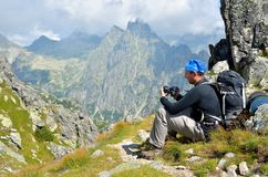 Resting hiker on a mountain trail. Stock Photos