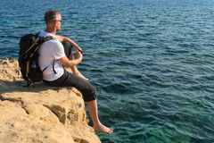 Resting hiker sits on a rocky sea shore Stock Image