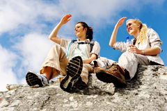 Resting hikers. Two women take a break from trekking and rest on a rock outdoors royalty free stock photo