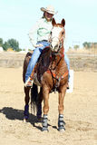 Resting Horseback Rider. A barrel racing horse and rider in an outdoor arena. The rider is a female wearing a cowboy hat. The horse and rider rest after a run Royalty Free Stock Photo