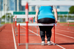 Resting on hurdle. Fat woman in activewear sitting on hurdle on stadium Stock Image