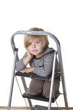 Resting on the ladder. Young boy wearing striped shirt and hood, sitting on a ladder, smiling at the camera Royalty Free Stock Photo