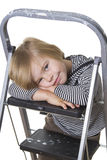 Resting on the ladder. Young boy wearing striped shirt and hood, sitting on a ladder, smiling at the camera Stock Image