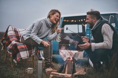 Resting after a long road. Beautiful young couple roasting marshmallows over a campfire while enjoying their road travel Stock Photos