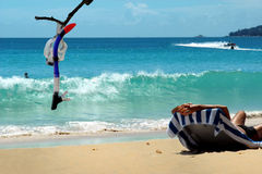 Resting man & diving mask on sea beach. Stock Photo