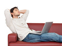 Resting man with laptop sits on the divan Stock Images