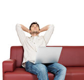 Resting man with laptop sits on the divan Royalty Free Stock Photos