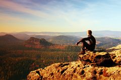 Resting man at the top of rock with aerial view of the deep misty valley bellow Stock Image
