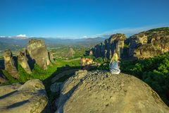 Resting at Meteora overlook. Woman traveler resting at Meteora landscape resting at Meteora overlook in Thessaly, Greece. Female hiker sitting on a rock on oper stock photo