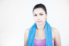 Resting over a workout. A beautiful brunette resting over a workout. Wearing a blue towel over the neck Royalty Free Stock Photography