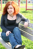 Resting On A Park Bench. Pretty teen girl resting on a park bench, serious expression royalty free stock photography