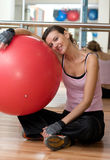 Resting from Pilates. A beautiful young woman resting on her exercise ball after a Pilates Workout Royalty Free Stock Image