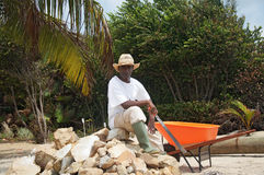 Resting on a pile of stones. A local man sits for a rest on a pile of rocks in the Caribbean Royalty Free Stock Photos