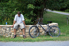 Resting Place. Tired man resting on stone wall next to bike Stock Photos