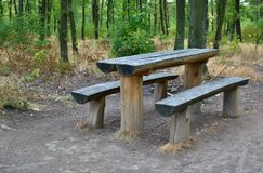 A resting place with benches and a table in the woods. Forest with a place to rest and a seating for tourists royalty free stock photography