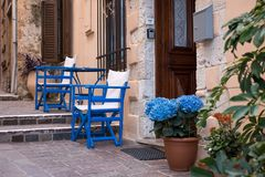Resting place with blue chairs on the narrow street in Greece. In summer royalty free stock image
