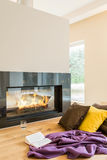 Resting place by the fireplace in apartment Stock Image