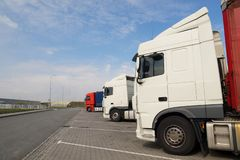 Various types of trucks in the parking lot next to the motorway stock photos