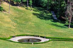 Resting place with wooden benches at a round fountain. Resting place with wooden benches at a round fountain with hedges below in the meadow stock photo