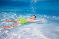 Resting on the pools bottom. Young man in shirts resting laying underwater on the pool bottom Royalty Free Stock Photo