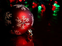 Resting Red Snowflake Bauble. A single red christmas ornament illuminated on glossy red paper Royalty Free Stock Photos