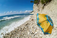 Resting on rocky beach under umbrella Royalty Free Stock Images