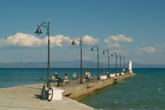 Resting on the sea quay. The photograph is more people in nice sunny day rest sitting on the benches on the quay in Pefkochori - Grece Stock Photo
