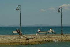 Resting on the sea quay. The photograph is more people in nice sunny day rest sitting on the benches on the quay in Pefkochori - Grece Stock Photos