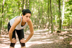 Resting after sport. Tired young woman resting after jogging in nature Stock Photography