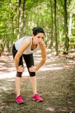 Resting after sport. Tired young woman resting after jogging in nature Stock Photo