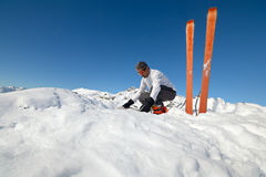 Resting on the summit. Alpinist watching a map on the summit. Pair of back country ski with sealskin Royalty Free Stock Photography