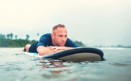 Resting surfer man on the board Stock Photos