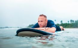 Resting surfer man on the board Royalty Free Stock Photos