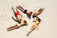 Resting teens. Image of five young people resting on the sand Royalty Free Stock Image