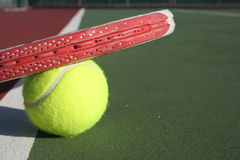 Resting Tennis Racquet. Tennis racquet resting on top of a ball on green and red court Stock Photo