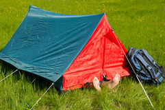 Resting in tent. A man resting in forest with his feet in the warm sun Royalty Free Stock Photography