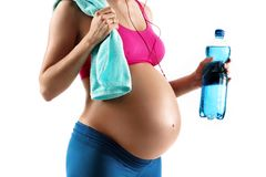 Close up of pregnant woman in sportswear holding towel and bottle of water isolated on white background. Resting time. Close up of pregnant woman in sportswear royalty free stock images